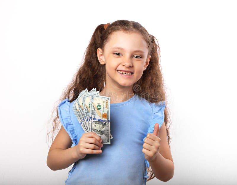 Gelukkig het glimlachen rijk de holdingsgeld van het jong geitjemeisje en het tonen van duim op s stock afbeeldingen