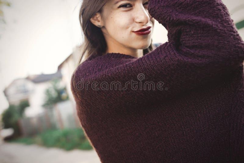 Gelukkig hipster onbezorgd meisje die in sweater in de stad van de avondzomer lopen Modieus Boheems meisje met grappige emoties d stock afbeelding