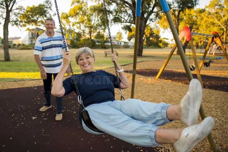 Gelukkig hoger Amerikaans paar rond 70 jaar het oude genieten van bij schommelingspark met vrouwen duwende echtgenoot die en pret royalty-vrije stock afbeeldingen