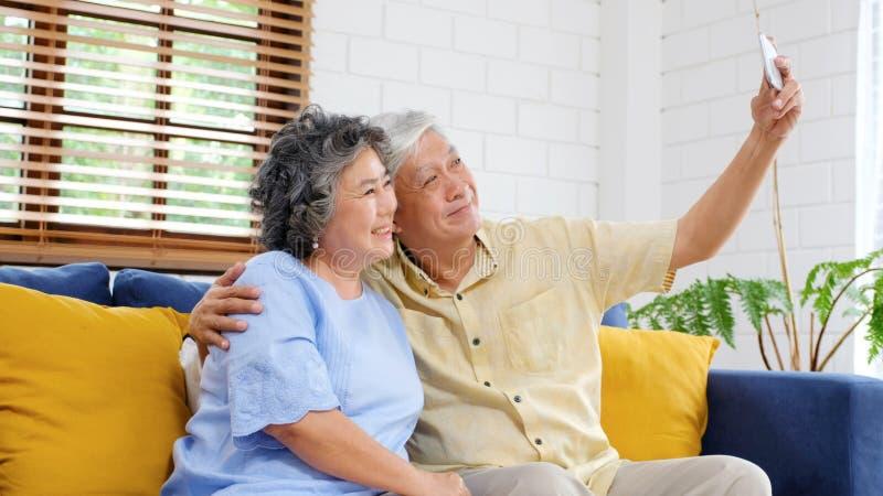 Gelukkig hoger Aziatisch paar die selfie thuis woonkamer, actieve hogere mensen in gelukkig ogenblik, toevallige pensioneringsmen royalty-vrije stock afbeeldingen