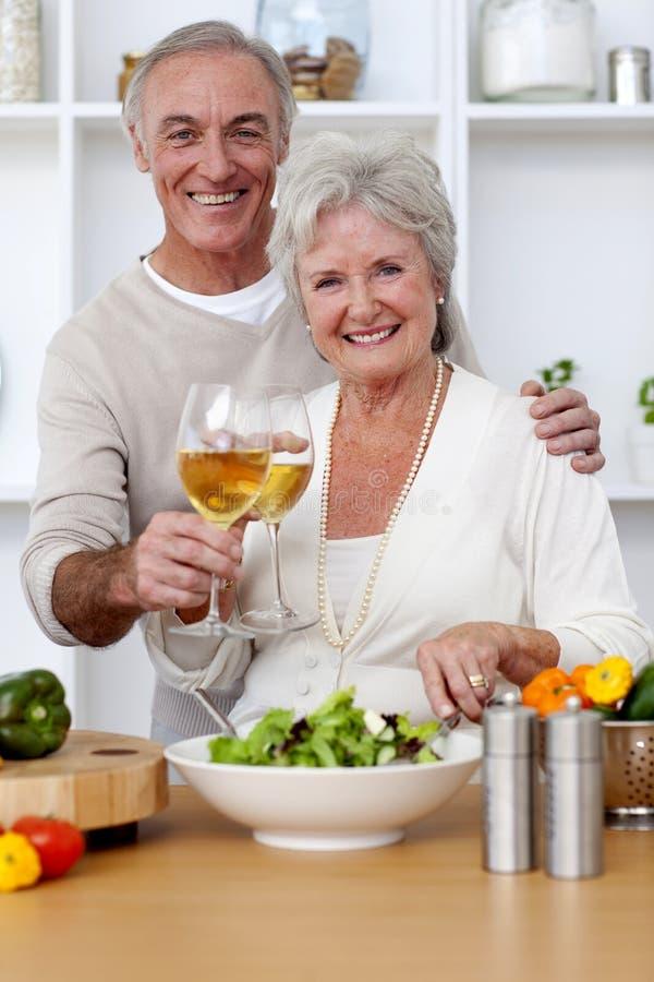 Gelukkig hoger paar dat een salade in de keuken eet royalty-vrije stock foto's