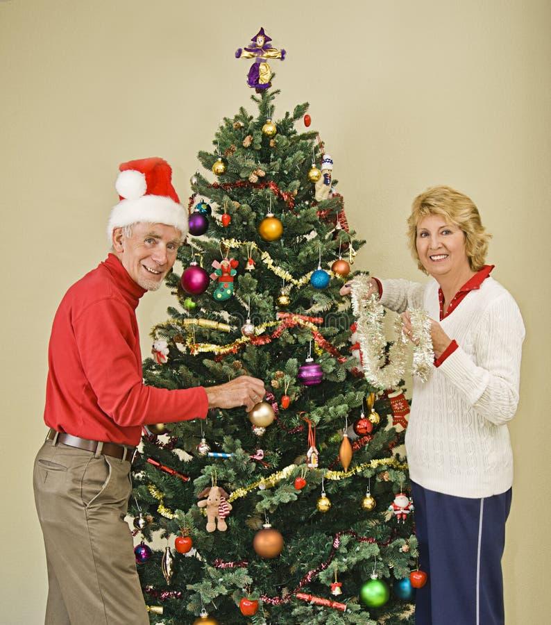 Gelukkig hoger paar dat Kerstboom verfraait royalty-vrije stock fotografie
