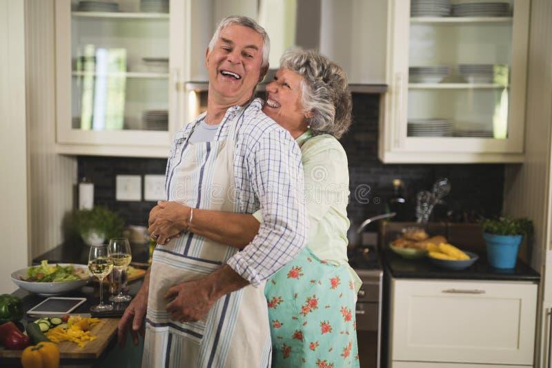 Gelukkig hoger paar die in keuken omhelzen royalty-vrije stock afbeeldingen