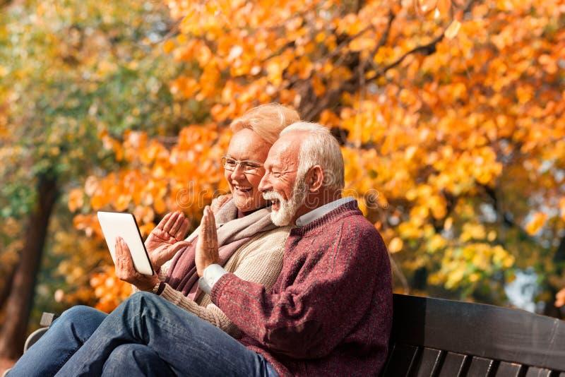 Gelukkig hoger paar die met hun grandkids via tablet in a spreken royalty-vrije stock fotografie