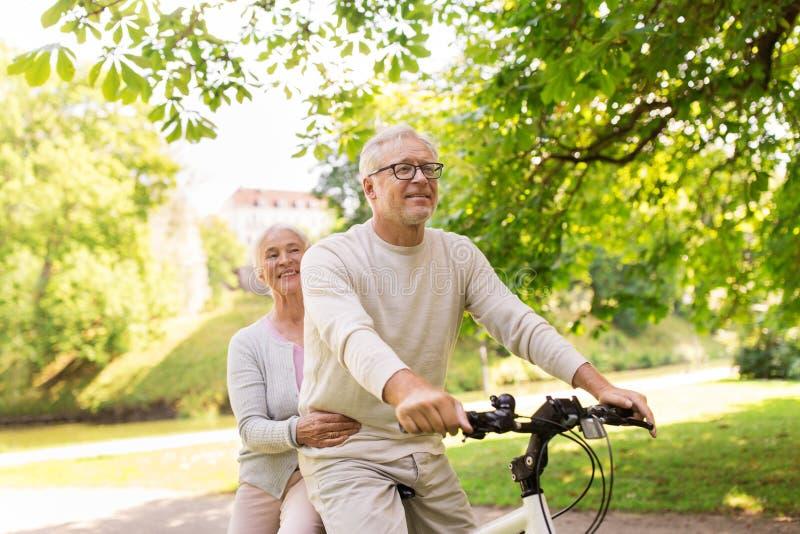 Gelukkig hoger paar die op fiets bij park berijden royalty-vrije stock afbeelding