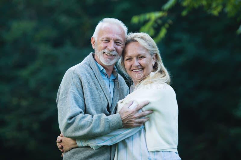 Gelukkig hoger paar die in openlucht in aard glimlachen royalty-vrije stock afbeeldingen