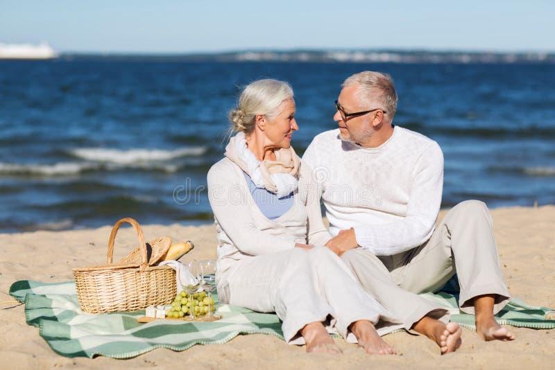 Gelukkig hoger paar die picknick op de zomerstrand hebben royalty-vrije stock afbeelding