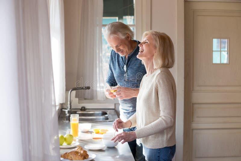Gelukkig hoger paar die pret hebben die ontbijt in kitche voorbereiden stock afbeelding