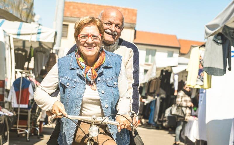 Gelukkig hoger paar die pret op fiets hebben bij stadsmarkt - Actieve speelse bejaarde concepten berijdende fiets in pensionering royalty-vrije stock foto's