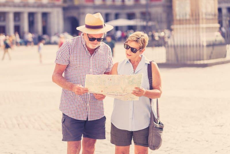 Gelukkig hoger paar die richtingen zoeken die een kaart op vakantie in een Europese stad gebruiken royalty-vrije stock afbeelding