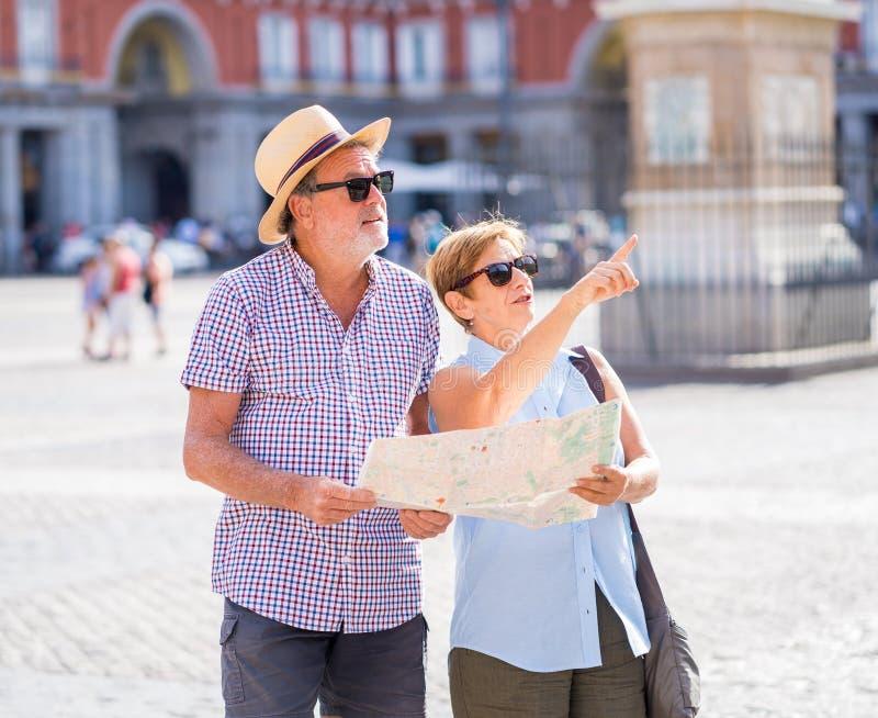 Gelukkig hoger paar die richtingen zoeken die een kaart op vakantie in een Europese stad gebruiken stock foto