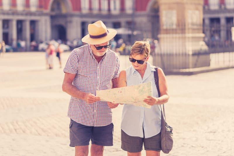 Gelukkig hoger paar die richtingen zoeken die een kaart op vakantie in een Europese stad gebruiken royalty-vrije stock foto's