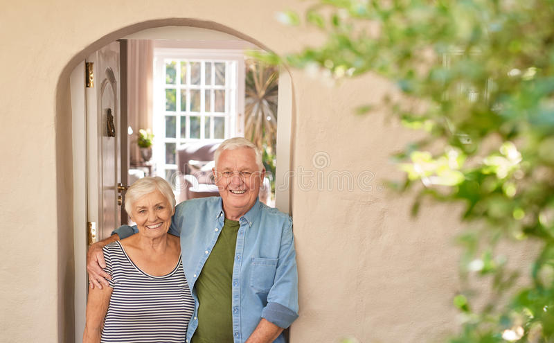 Gelukkig hoger paar die welcomingly bij hun voordeur glimlachen royalty-vrije stock foto
