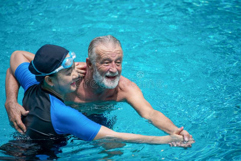 Gelukkig Hoger paar die in Zwembad samen dansen Het hebben van pret De holdingshanden en het geknuffel, omhelzing, omhelzen, pens royalty-vrije stock foto