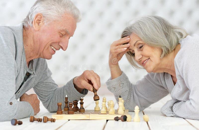 Gelukkig hoger paar het spelen schaak royalty-vrije stock afbeelding