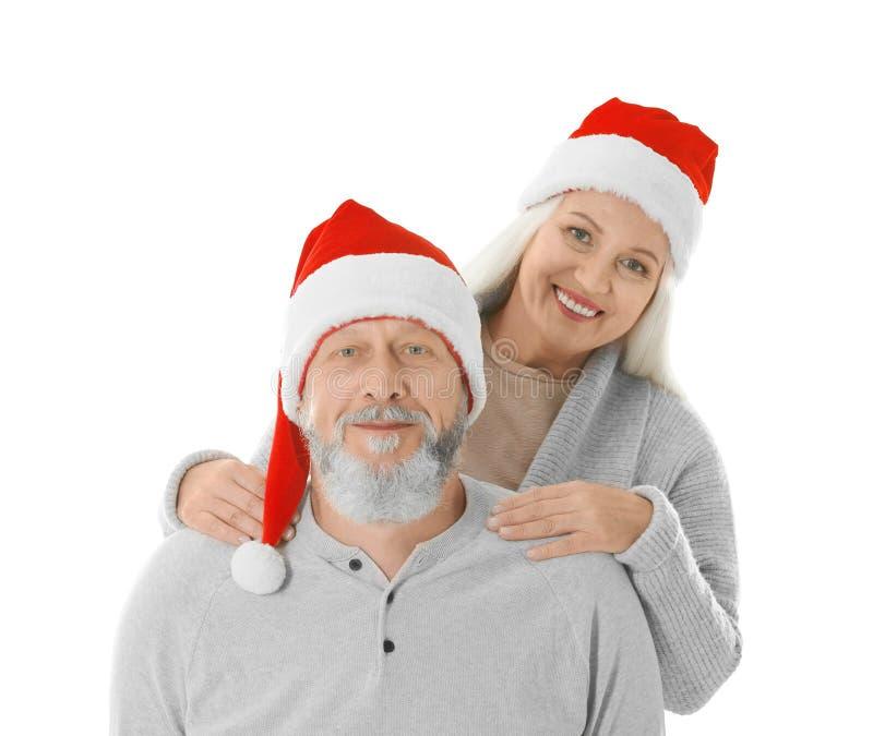 Gelukkig hoger paar met Kerstmishoeden op witte achtergrond stock fotografie