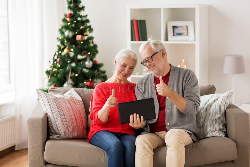 Gelukkig hoger paar met tabletpc bij Kerstmis royalty-vrije stock afbeelding
