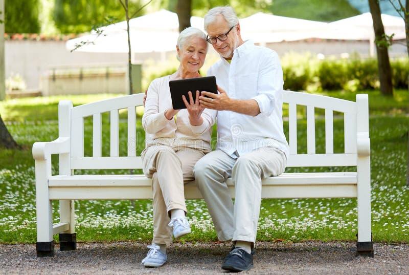 Gelukkig hoger paar met tabletpc in stadspark stock fotografie