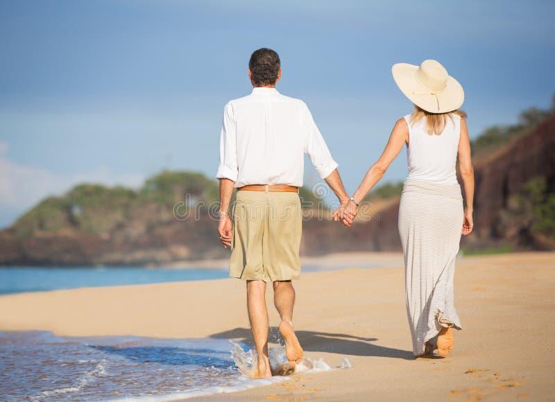 Gelukkig hoger paar op het strand. Pensioneringsluxe Tropisch Onderzoek stock fotografie