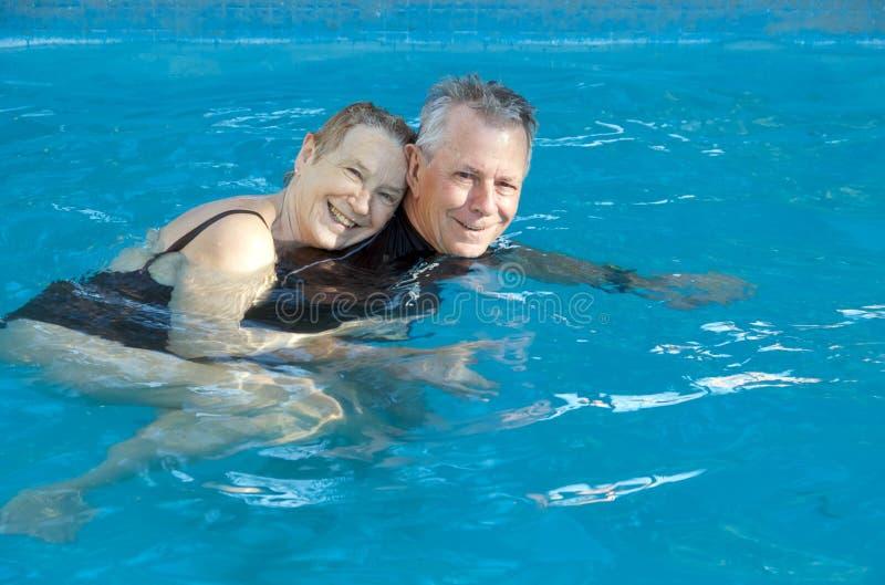 Gelukkig hoger paar in pool stock afbeelding