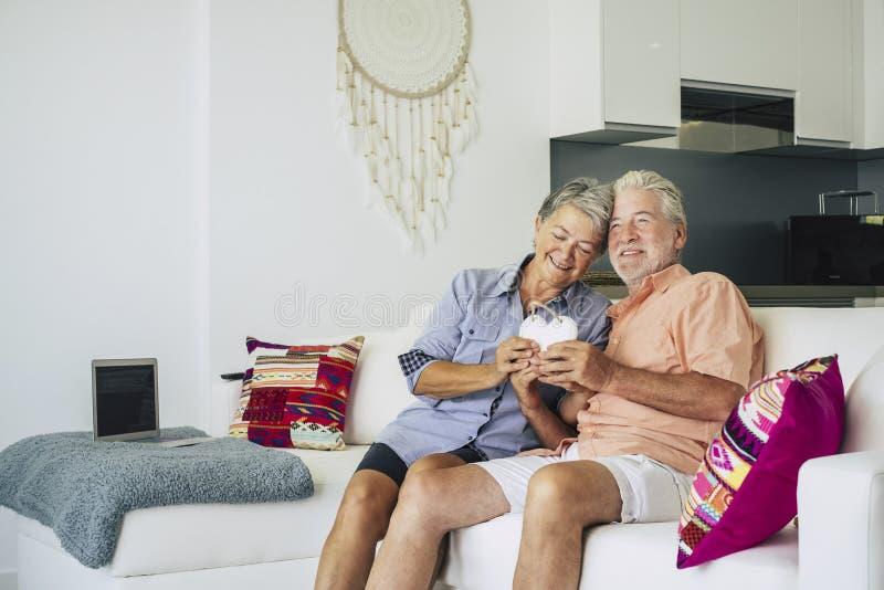 Gelukkig hoger volwassen paar van cacuasian mensen in liefdezitting thuis op de bank en het nemen van een houten hand - gemaakte  royalty-vrije stock foto