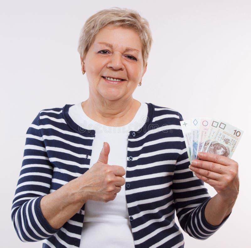 Gelukkig hoger vrouwelijk de muntgeld van het holdingspoetsmiddel en het tonen van duimen, financiële zekerheid in oude dag royalty-vrije stock fotografie