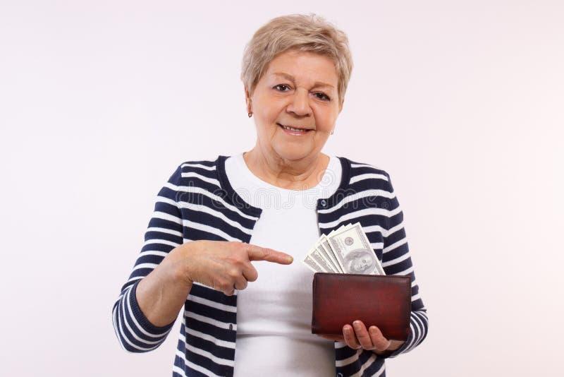Gelukkig hoger wijfje die dollarmunten in portefeuille tonen, concept financiële zekerheid in oude dag stock foto