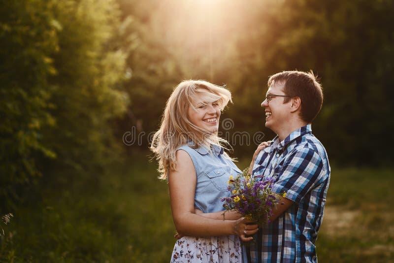 Gelukkig houdend van jong paar die in openlucht koesteren stock foto's