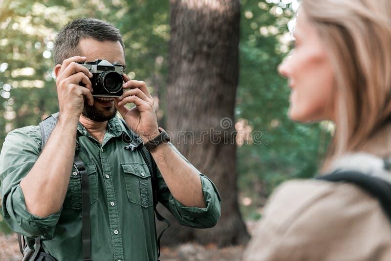 Gelukkig houdend van paar die camera in de aard met behulp van stock foto