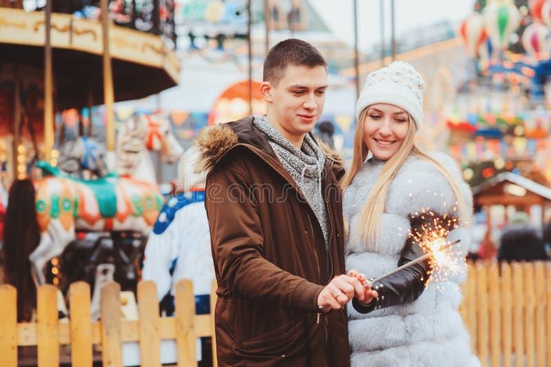 gelukkig houdend van paar die van Kerstmis of Nieuwe jaarvakantie genieten openlucht stock afbeeldingen