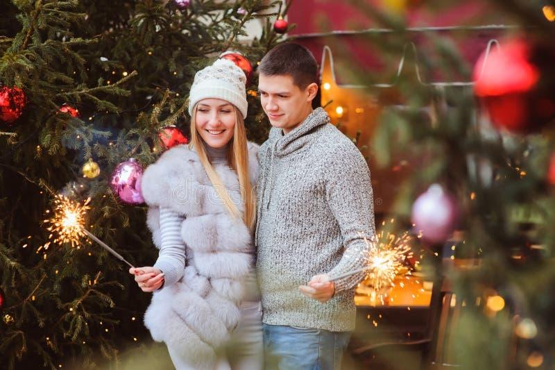 Gelukkig houdend van paar die van Kerstmis of Nieuwe die jaarvakantie openlucht op stadsstraten genieten voor viering worden verf royalty-vrije stock foto's