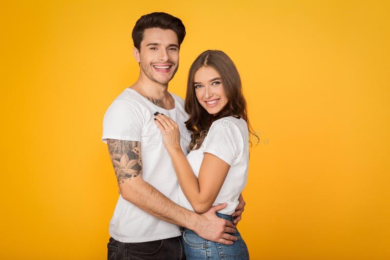 Gelukkig houdend van paar die tegen gele achtergrond omhelzen royalty-vrije stock afbeeldingen