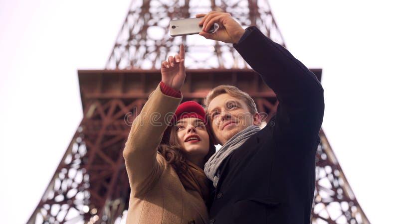 Gelukkig houdend van paar van toeristen die selfie op achtergrond van de Toren van Eiffel doen royalty-vrije stock afbeeldingen