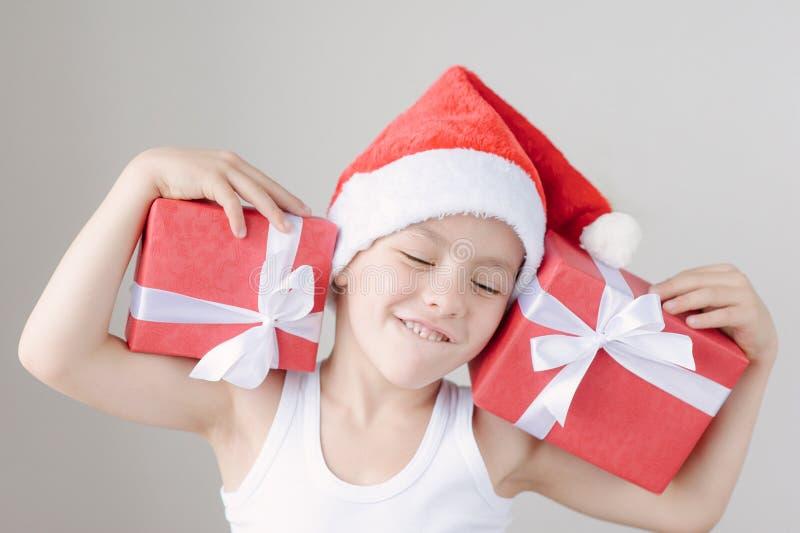Gelukkig houdt weinig jongen in Kerstman` s hoed en t-shirt dozen van giften stock foto