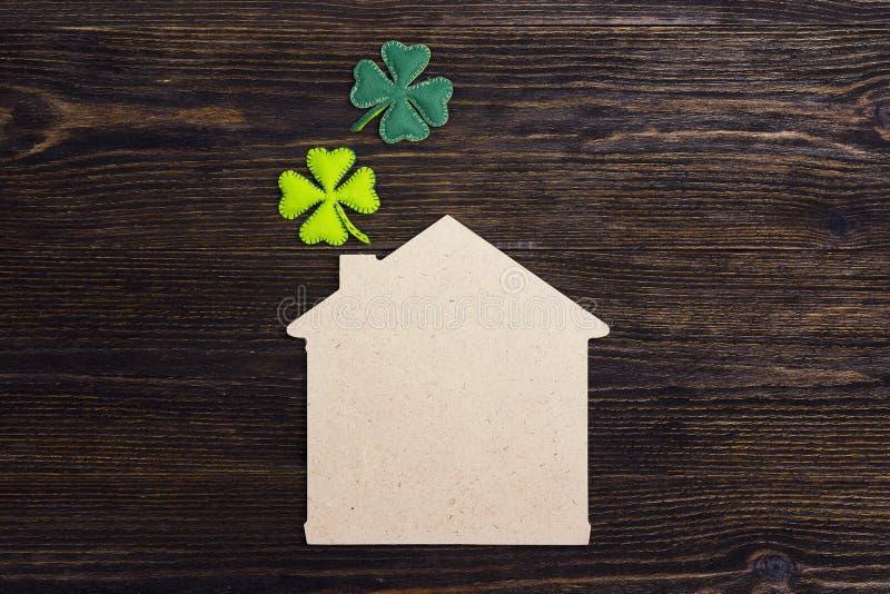 Gelukkig huissymbool met klavertjevier op houten achtergrond Co royalty-vrije stock foto
