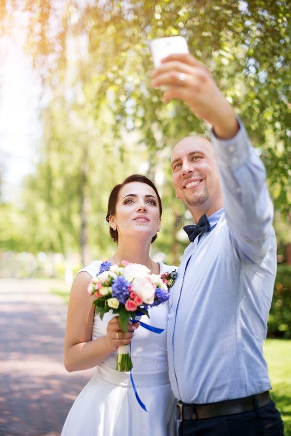 Gelukkig huwelijkspaar - bruid en bruidegom die selfie tijdens huwelijksceremonie in openlucht maken royalty-vrije stock afbeeldingen