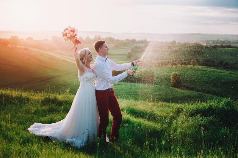 Gelukkig huwelijkspaar met buttle van champaine en plonsen van champagne royalty-vrije stock afbeeldingen