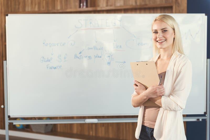 Gelukkig jeugdig meisje die nieuwe baanstrategieën in bureau leren royalty-vrije stock afbeelding
