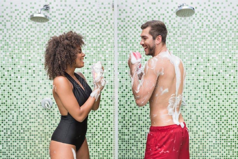 Gelukkig jeugdig paar die pret hebben terwijl binnen wassen royalty-vrije stock afbeelding