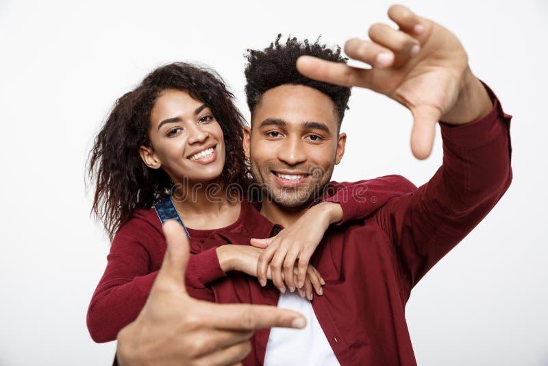 Gelukkig jong Afrikaans Amerikaans paar die door een vingerkader kijken en terwijl status geïsoleerd op wit glimlachen stock afbeelding