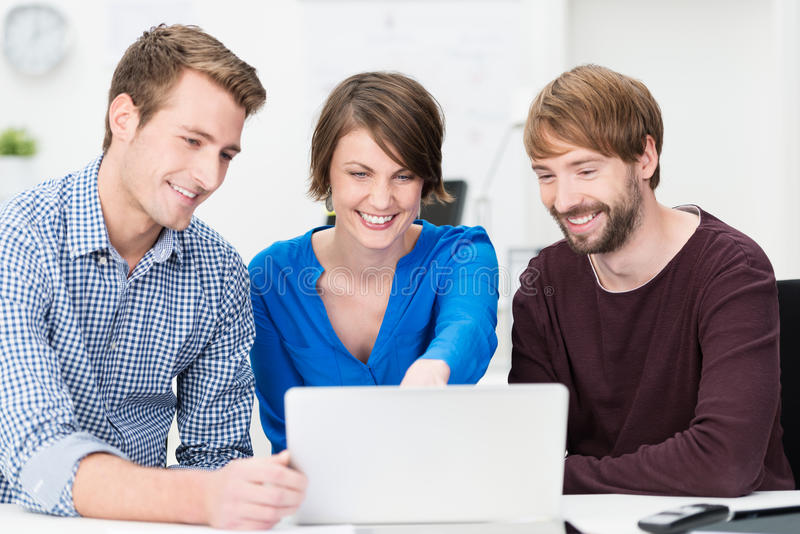 Gelukkig jong commercieel team die aan laptop werken stock afbeelding