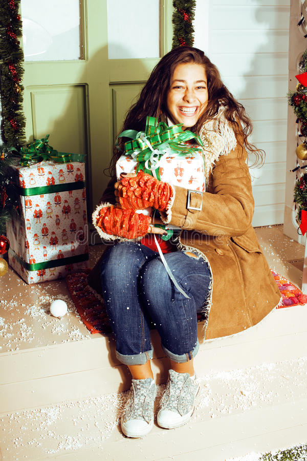 Gelukkig jong die meisje thuis op Kerstmis, brengende giften wordt verfraaid aan vrienden stock afbeelding
