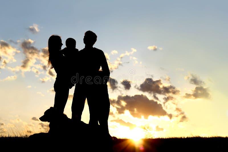 Gelukkig Jong Familie en Hondsilhouet bij Zonsondergang stock afbeeldingen