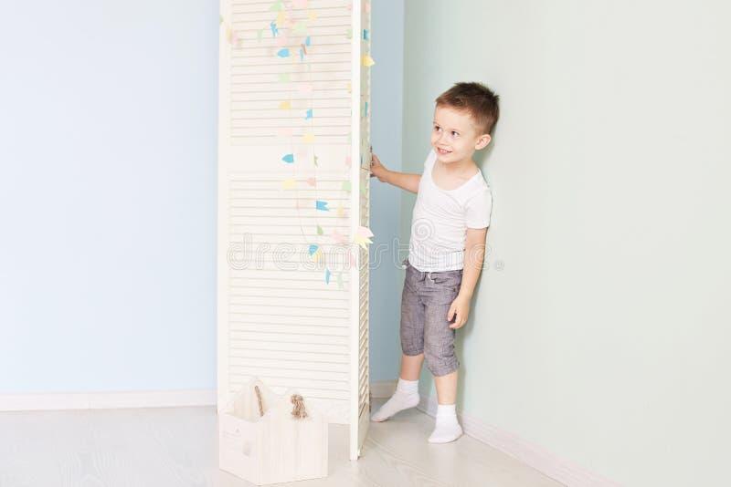 Gelukkig jong geitje achter deur de jongensspelen Hij verbergt achter de witte deur stock fotografie
