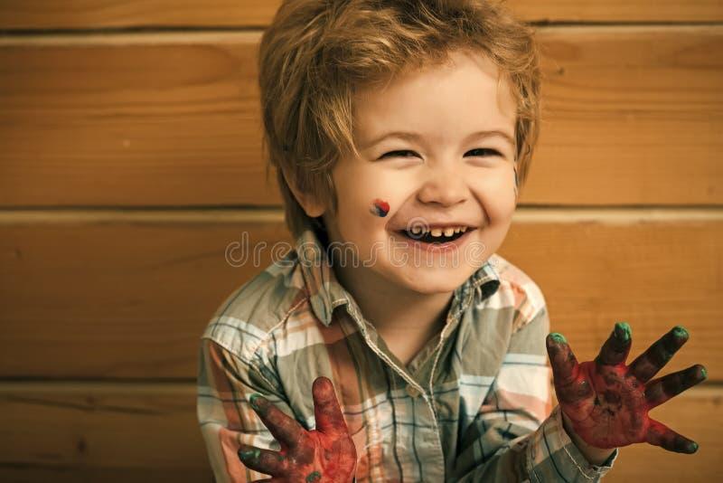 Gelukkig jong geitje die pret hebben Jongenskunstenaar het gelukkige glimlachen op houten muur royalty-vrije stock foto