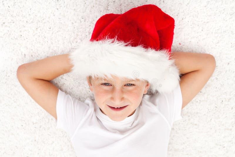 Gelukkig jong geitje in Kerstmistijd die op de vloer legt stock foto's