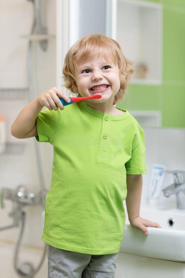Gelukkig jong geitje of kind die zijn tanden in badkamers borstelen Tand Hygiëne stock fotografie