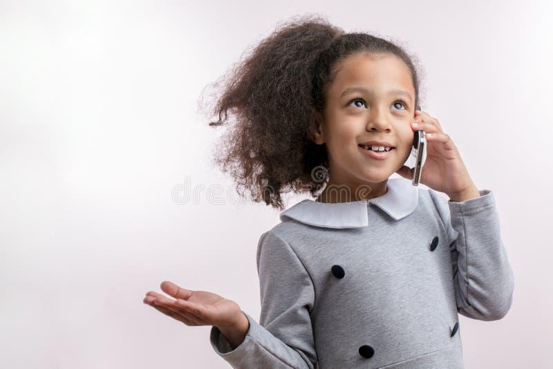 Gelukkig jong geitje met paardestaart gebruikend haar slimme telefoon en omhoog kijkend royalty-vrije stock afbeeldingen