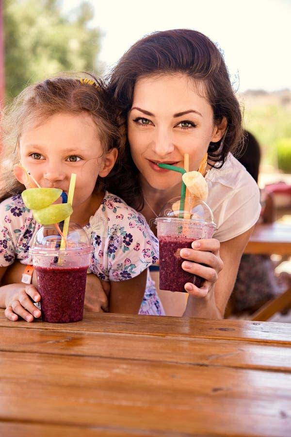 Gelukkig jong geitjemeisje en grappig emotioneel moeder het drinken bessen smoothie sap samen in straatkoffie close-up royalty-vrije stock foto's