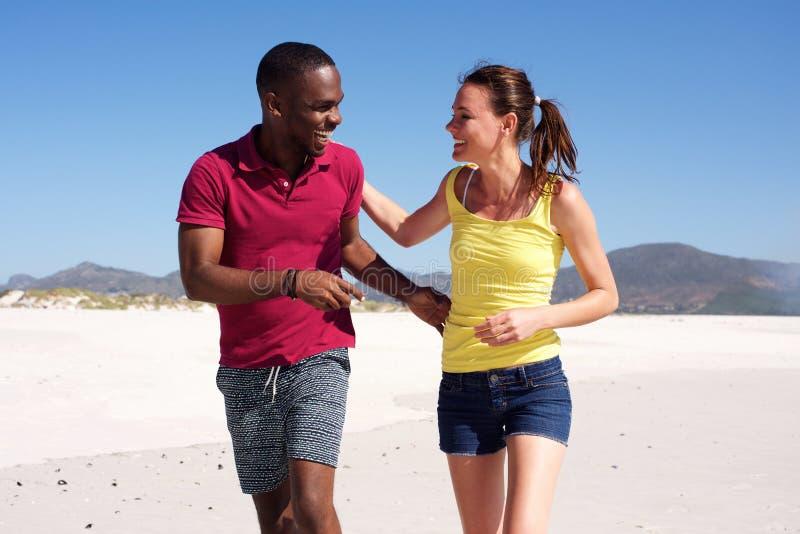 Gelukkig jong geschiktheidspaar die samen op strand lopen stock fotografie